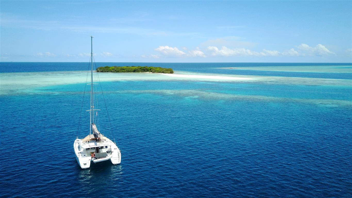 Anchoring in front of a stunning island aboard a Maldives Catamaran Charter | Elysia Yacht Charters