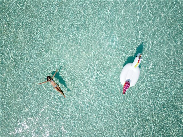 Drone shot of floating toy and floating guest in clear Maldivian water | Elysia Charters
