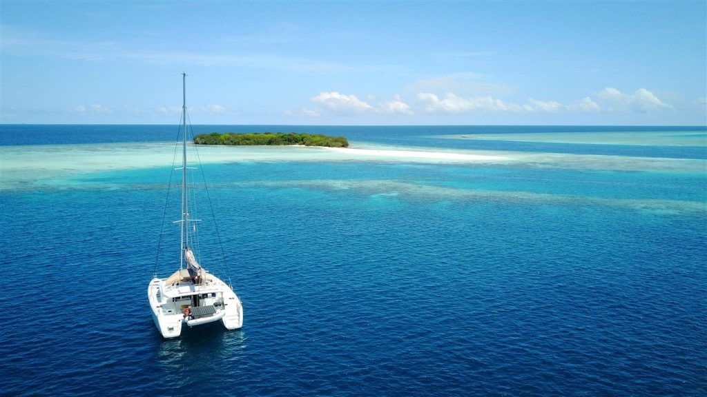 Anchoring in front of a stunning island aboard a Maldives Catamaran Charter   Elysia Yacht Charters